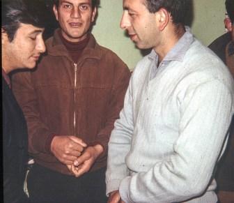 3 turkish guys gathered around the heater in the classroom.