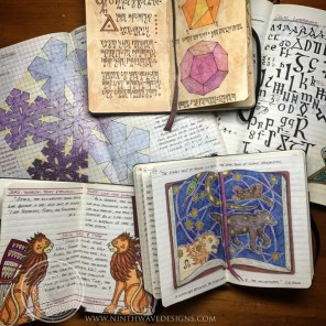An assortment of notebooks and sketchbooks, including the Alchemy Notebook, shown at the top center.