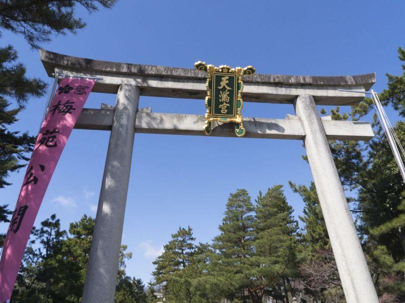 Une bannière accrochée à la gauche du torii annonce que les umes sont en fleurs à Kitano Tenmangū.