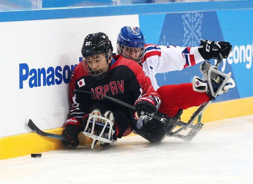 Uehara Daisuke (à gauche) se bat pour la rondelle contre un joueur de la République tchèque le 13 mars 2018, lors du premier tour de hockey sur luge sur glace aux Jeux paralympiques d'hiver de Pyeongchang. (© Jiji)