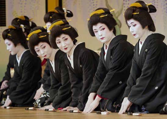 Mujeres vestidas con kimono negro de manga corta con mon y cuello blanco, con el pelo recogido al estilo Shimada-mage, como dictaba el reglamento de indumentaria para las geishas. La imagen corresponde al ensayo de la víspera del Azuma Odori, un recital que se representa en el Shinbashi Enbujō, un teatro que se fundó para exhibir los resultados de las prácticas de música y danza de las geishas de Shinbashi. (Mayo de 2019, Jiji Press.)