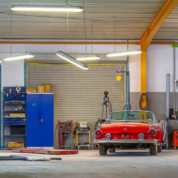 red vintage sports car in a car repair garage