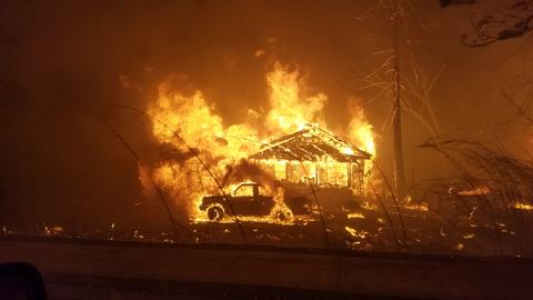 A house, truck and trees burn.
