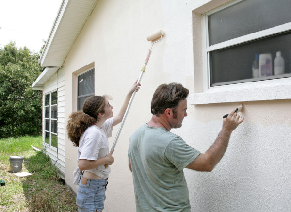 Woman and Man Painting House Exterior