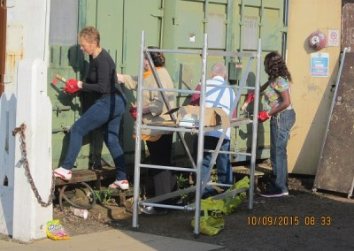 Nationwide Building Society volunteers Carol, Liz, Peta and John prepare the container doors for repainting. Photo: Grahame Every
