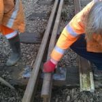 With screws put back in and the new check rail installed, Ian Nicholls supervises as David Millard backfills the ballast and inspects the new track work. Photo: Graham Peacock