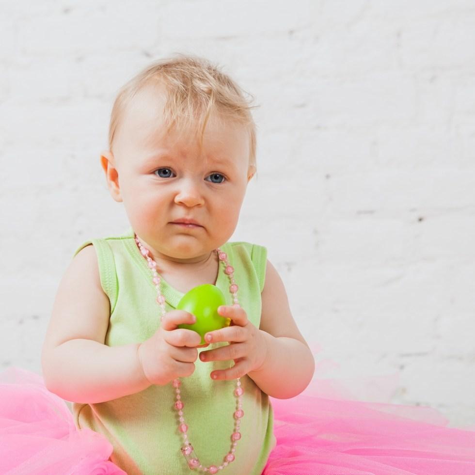 Sad baby girl holding toy