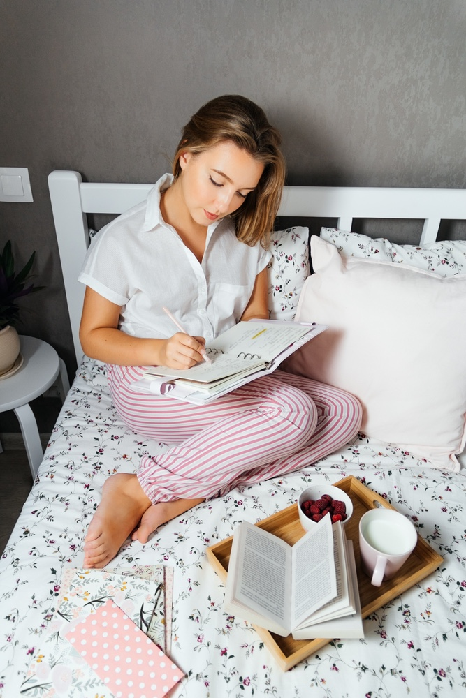 Mother writing in her journal with breakfast in bed