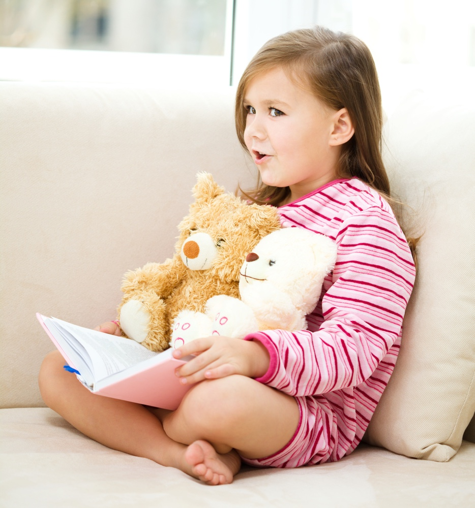 Little Girl reading to teddy bear