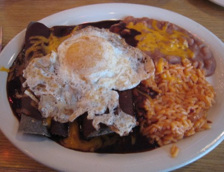 Blue corn enchiladas with red chile and a fried egg