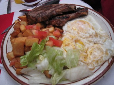 """""""El Jefe"""" - two grilled pork chops, two eggs (any style) and fried potatoes."""