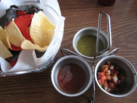 Three salsas with red, yellow and blue corn chips
