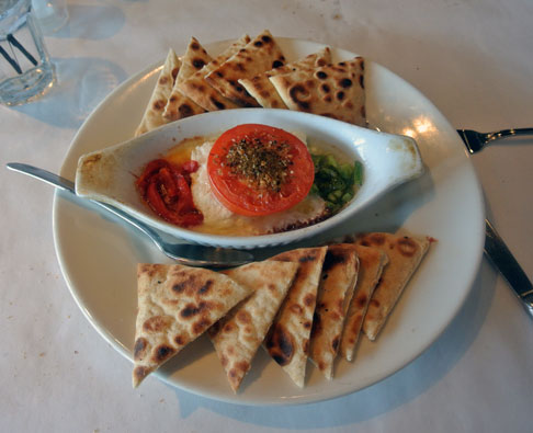 Feta Psiti: Baked Feta with peppers, tomato & olive oil; Served with pita wedges