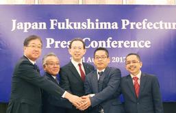 コメの輸出拡大合意で、関係業者と握手をする内堀福島県知事(中央)=23日、クアラルンプール(NNA撮影)
