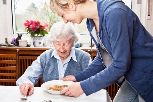 senior woman getting soup served by young home caregiver