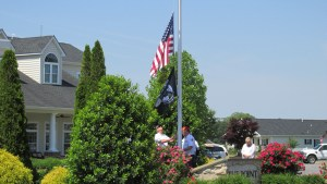 Walt Waite and Bob Sly raise the American Flag and the POW Flag; Colleen Ostafy stands to the right