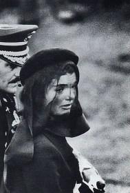 *** Arlington, 1963 – di Elliott Erwitt – Jacqueline Kennedy lascia il Cimitero dove si è appena conclusa la cerimonia funebre del Presidente. Il volto contratto della Signora, fortemente segnato dal dolore, si materializza nell'obiettivo di Erwitt, fortunato per questa opportunità offertagli dal caso. L'abilità del Maestro è nell'avere catturato, insieme, il volto della Signora, appena anteposto a quello fisiognomicamente somigliante dell'Ufficiale che la scorta. Entrambi sono contemporaneamente in scena sulla metà di sinistra del fotogramma ed hanno davanti a loro uno spazio vuoto che è coerente con l'atmosfera del momento.