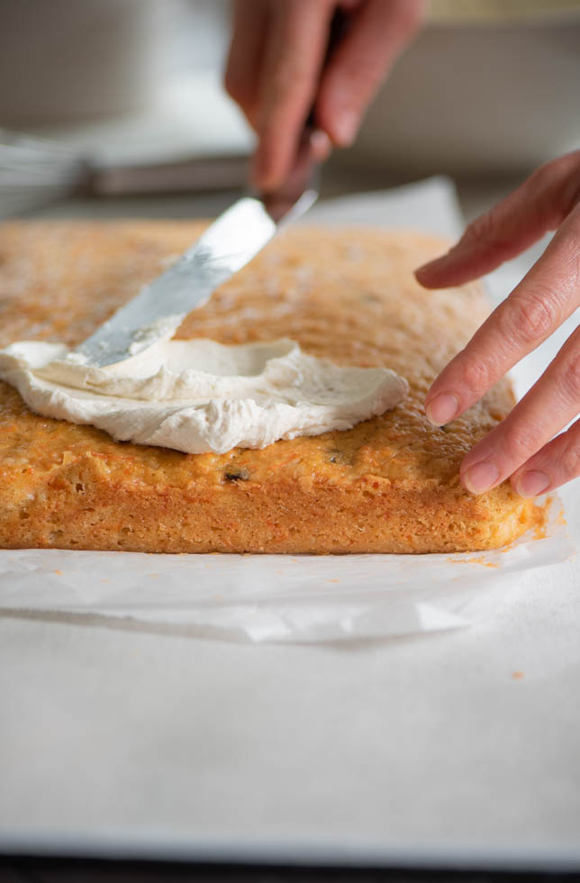 45 angle of hand spreading frosting on carrot cake with spatula