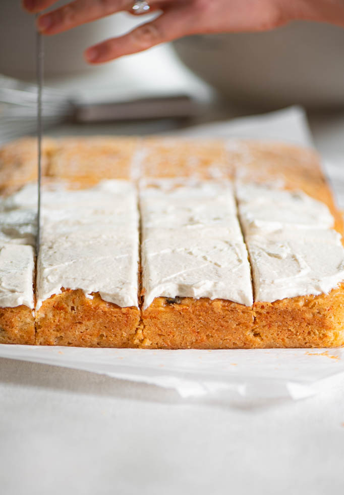 cutting into frosted carrot cake