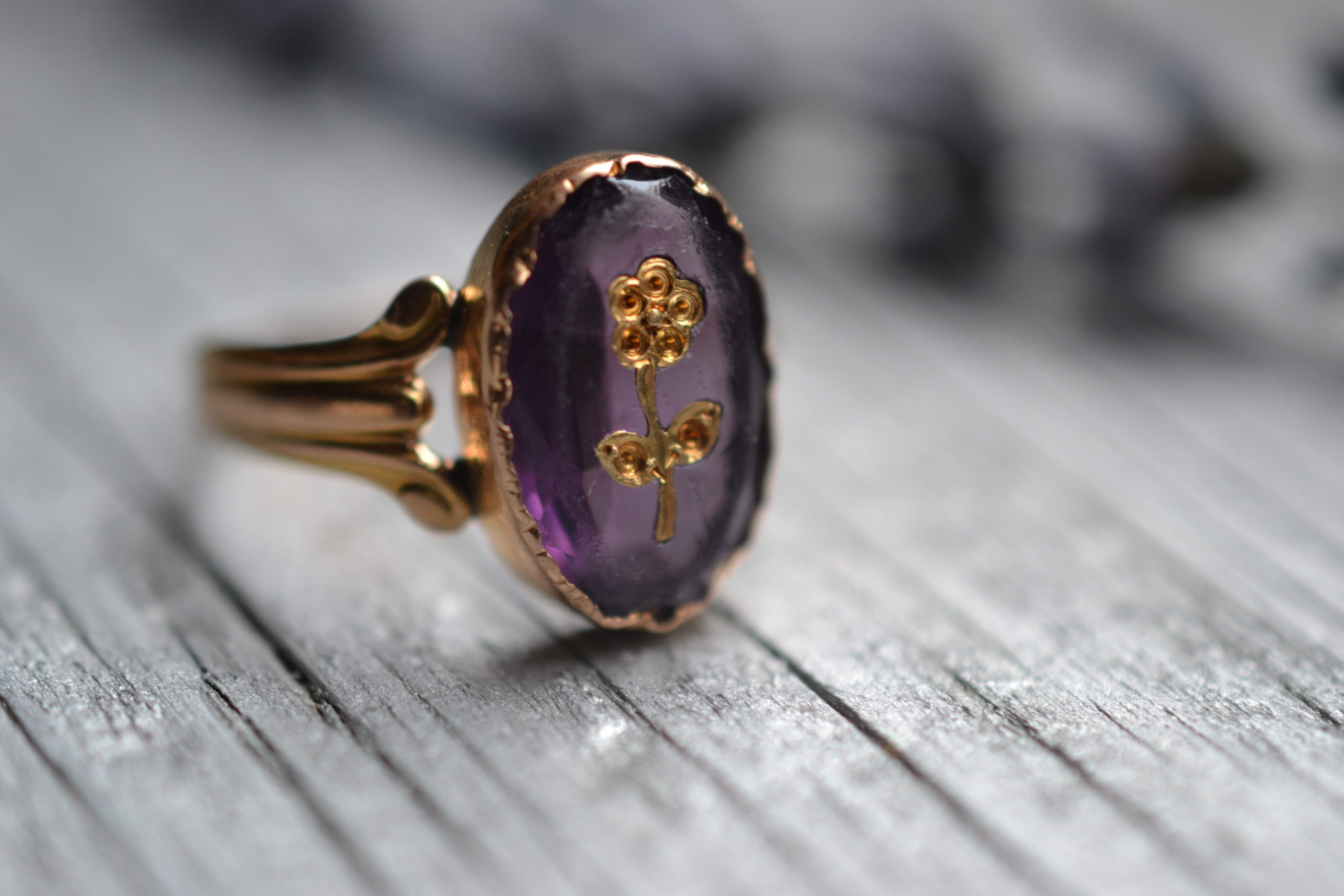 Bague vintage en or jaune 18 carats (750/1000), sertie d'une pierre violette et gravée d'une fleur - un bijou Noircarat.fr