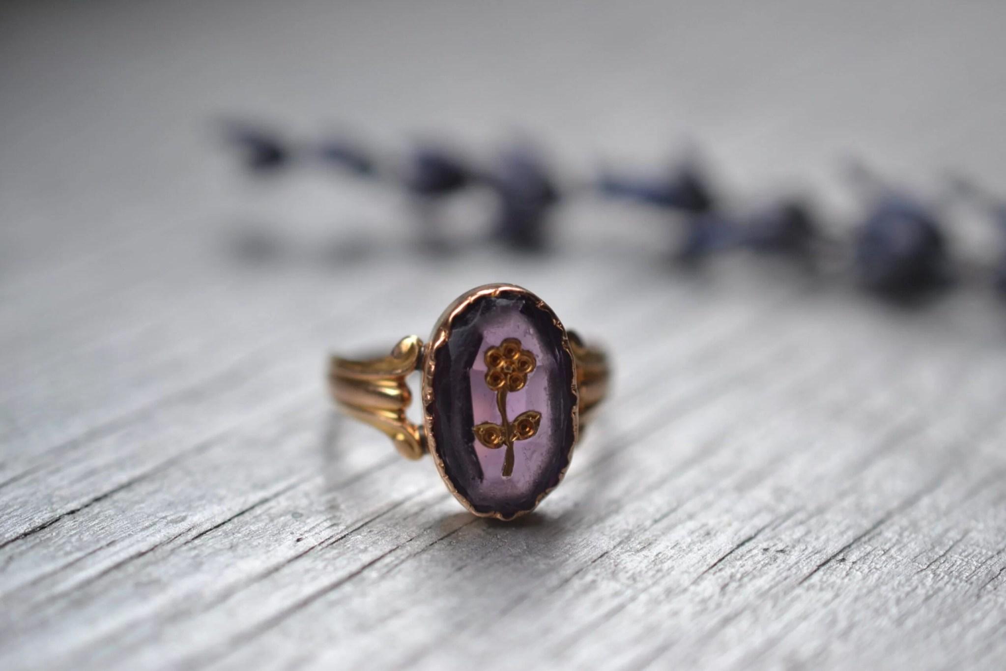 Bague vintage et ancienne en or jaune 18 carats (750/1000), sertie d'une pierre violette et gravée d'une fleur