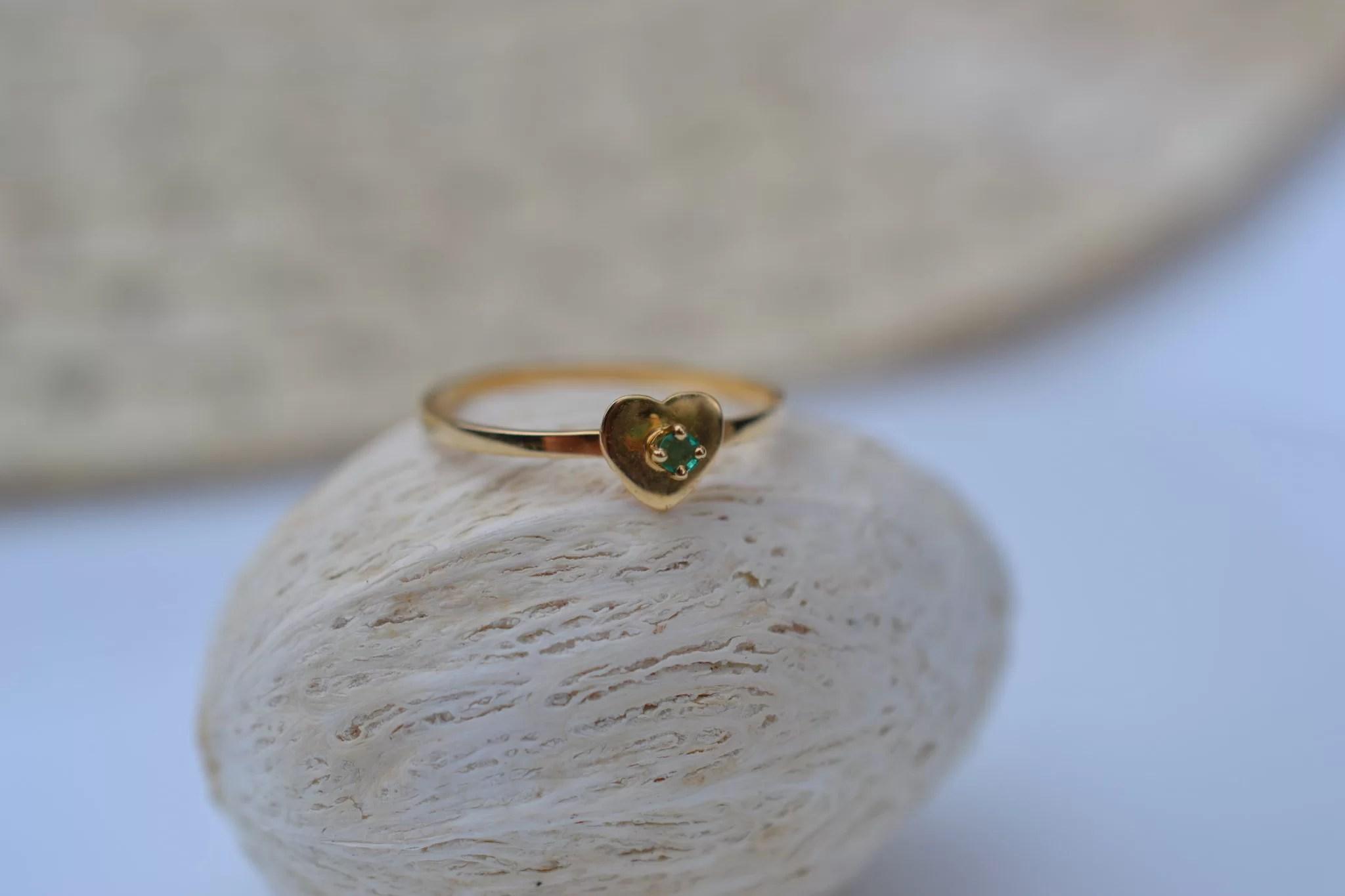 Bague en Or jaune sertie d'une pierre verte sur une monture en forme de cœur bijou seconde main