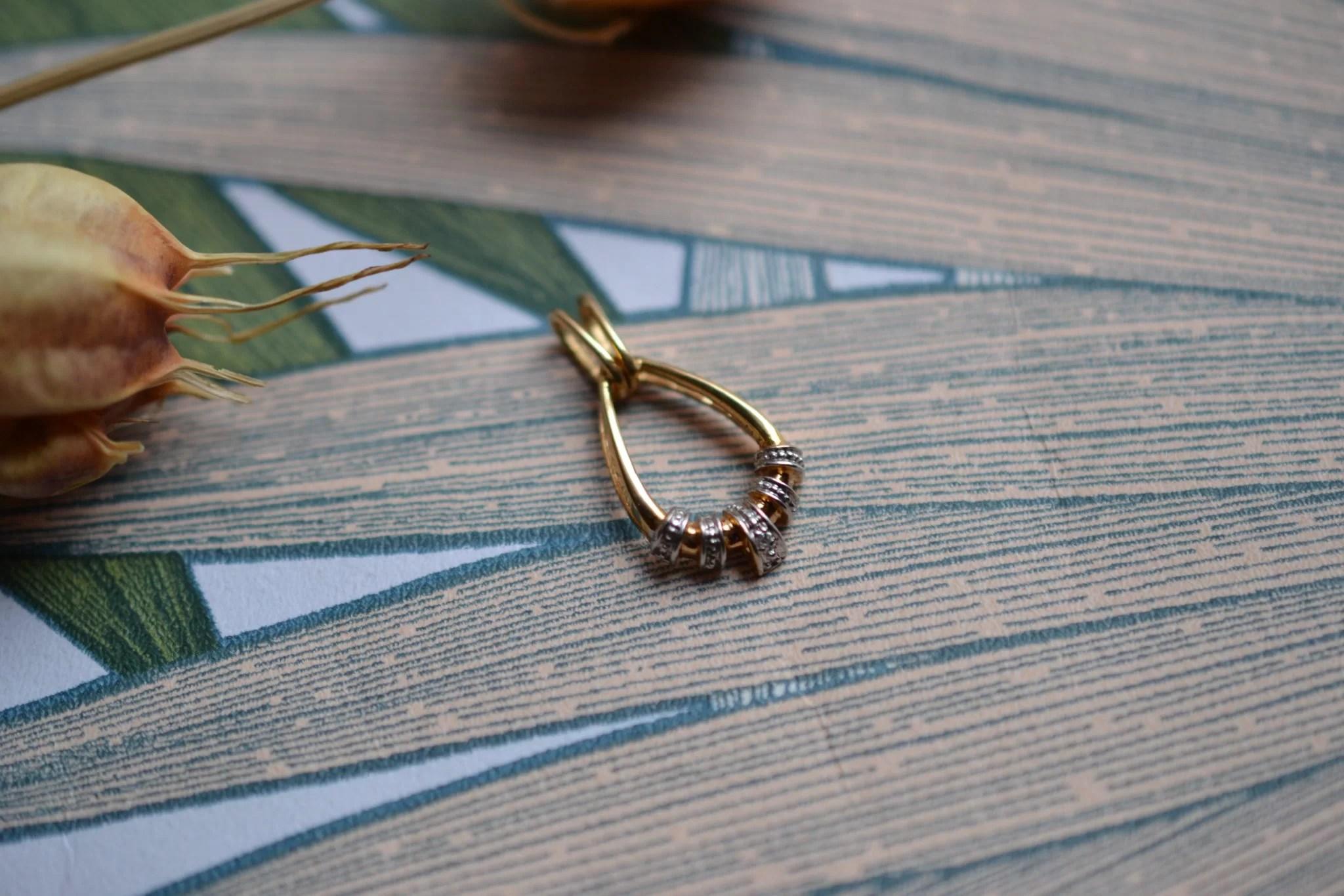 Pendentif en Or jaune et Or blanc en forme de goutte ajourée serti d_un diamant, avec un effet pavage pierres - bijou rétro
