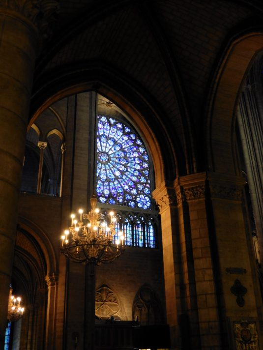 Windows and chandeliers inside of Notre Dame cathedral in Paris, France