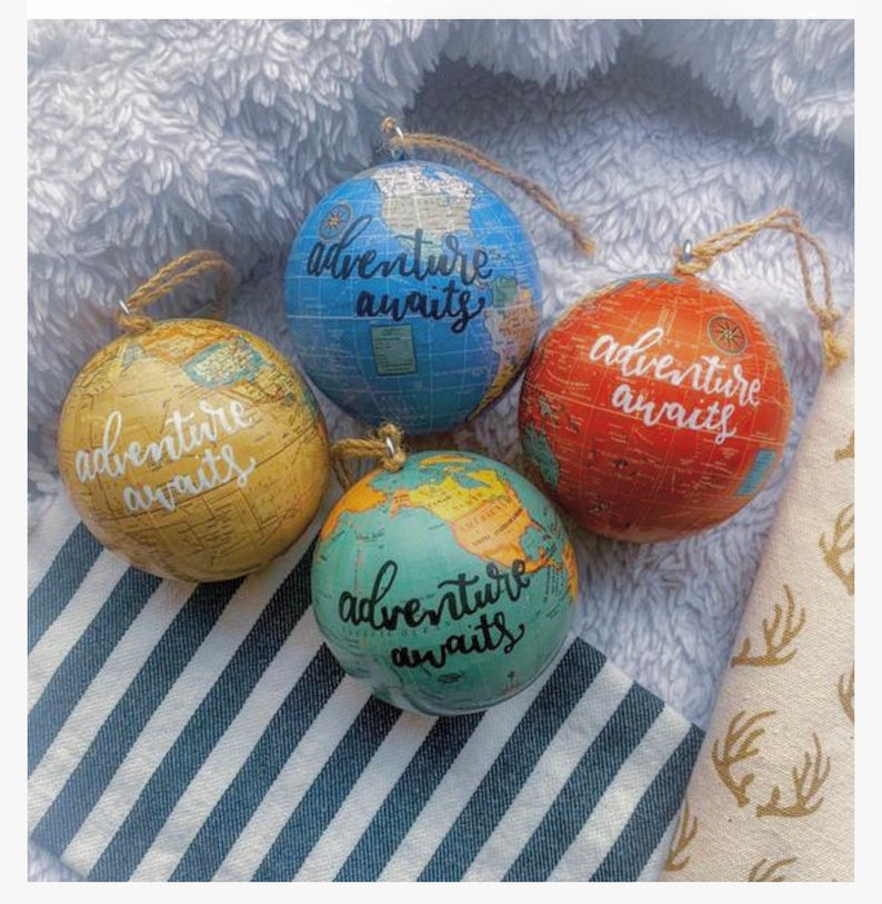 """Multi-colored globe ornaments with text reading """"Adventure awaits"""""""