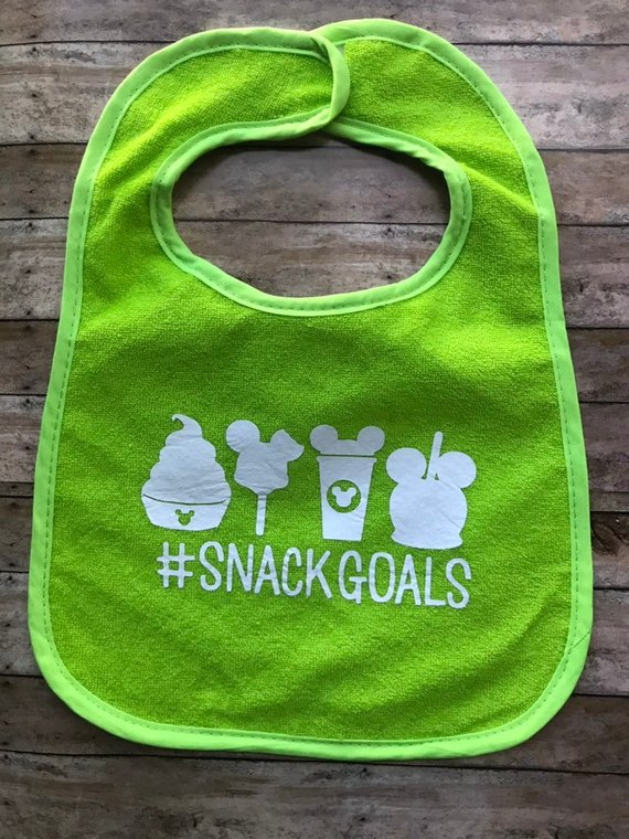 Green baby bib with Disney snacks printed on it