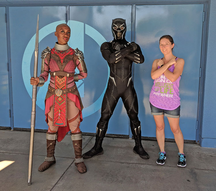 Woman posing with Black Panther and one of the Dora Milaje warriors at California Adventure