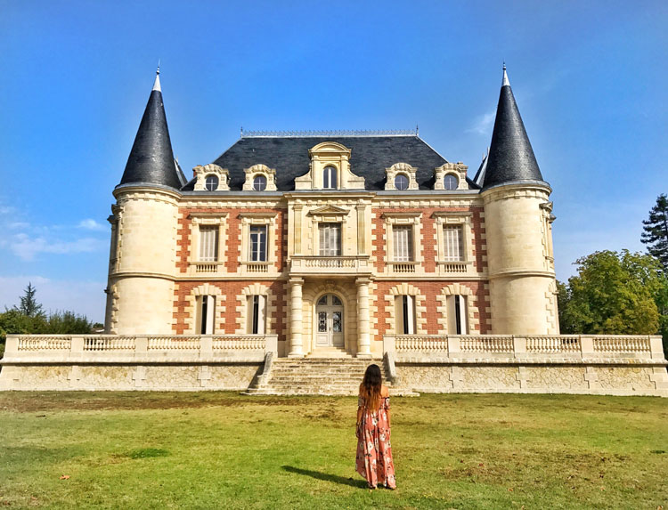 Woman standing in front of a winery in Bordeaux