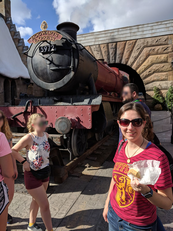 Woman holding butterbeer fudge in front of the Hogwarts Express in the Wizarding World of Harry Potter