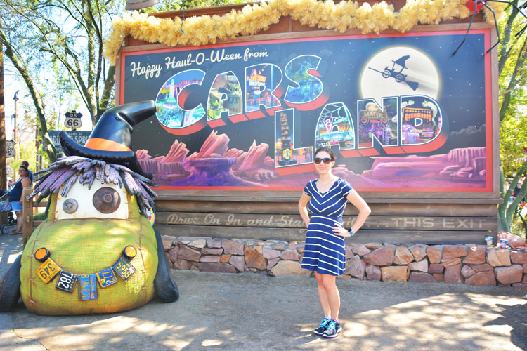 Woman posing with Halloween decorations in California Adventure's Cars Land