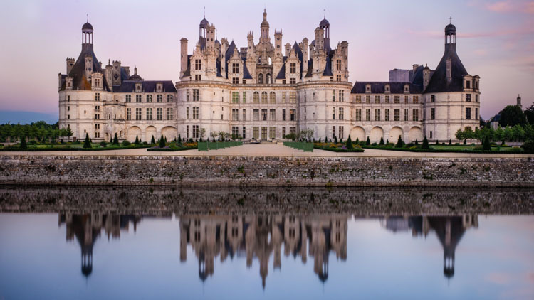 Chateau Chambord reflected in water at dusk