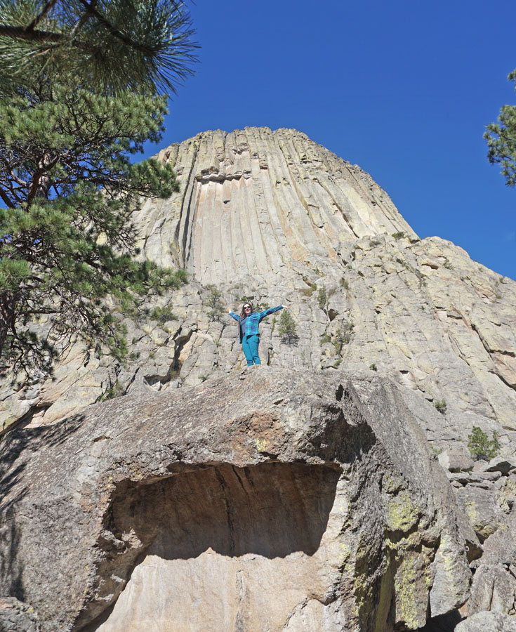 Woman standing on boulders in front of Devils Tower Wyoming