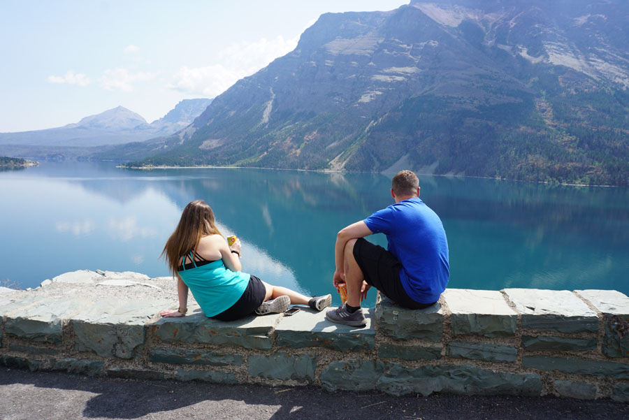 Visitors sitting in front of a turquoise mountain lake in Glacier National Park
