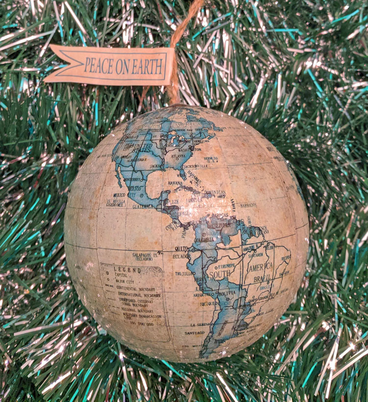 "Globe travel ornament with flag saying ""peace on earth"""