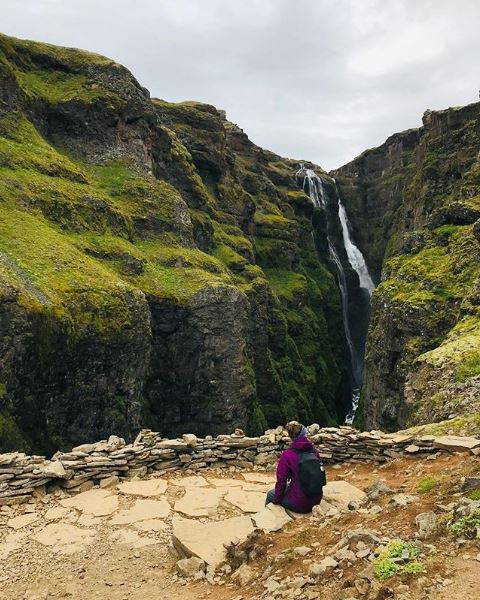 Woman sitting in front of Glymur waterfall in Iceland