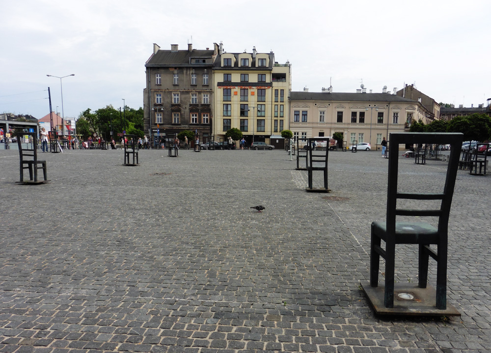 Empty metal chairs in a cobblestone square honoring Jews murdered during WWIII