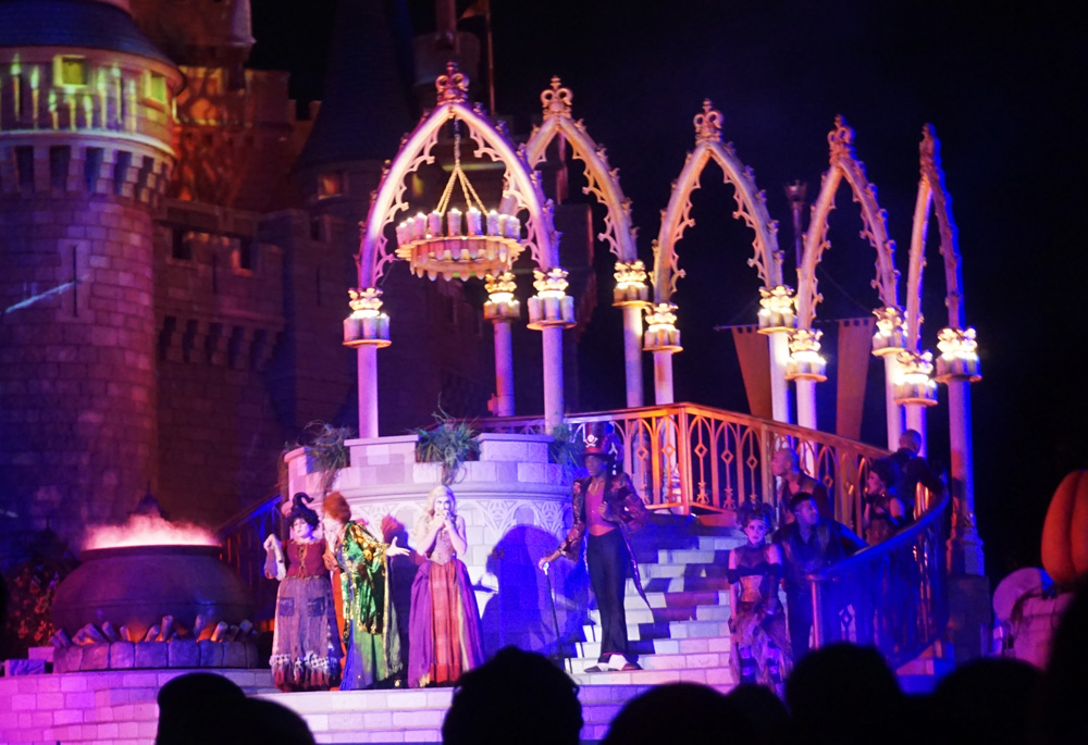 Sanderson Sisters performing onstage in front of Cinderella Castle