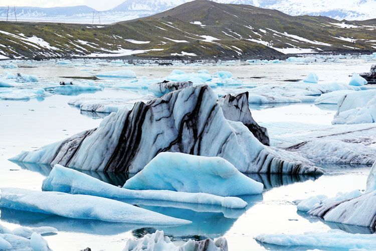 Icebergs in Jokulsarlon striped with volcanic ash