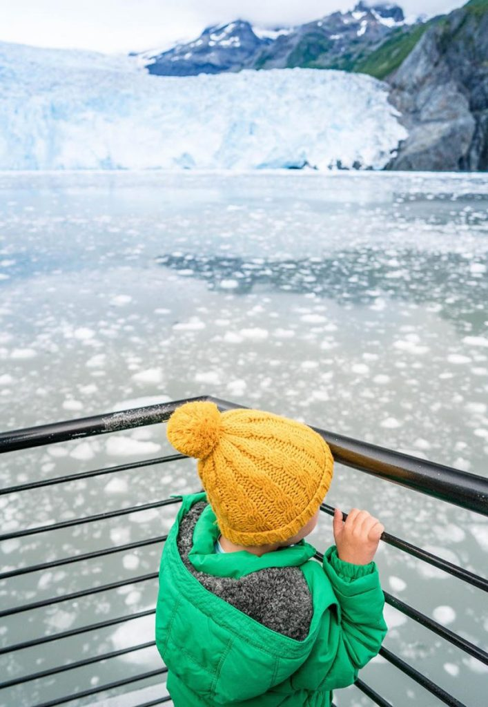 Kid in a colorful hat standing in front of a glacier in Kenai Fjords National Park