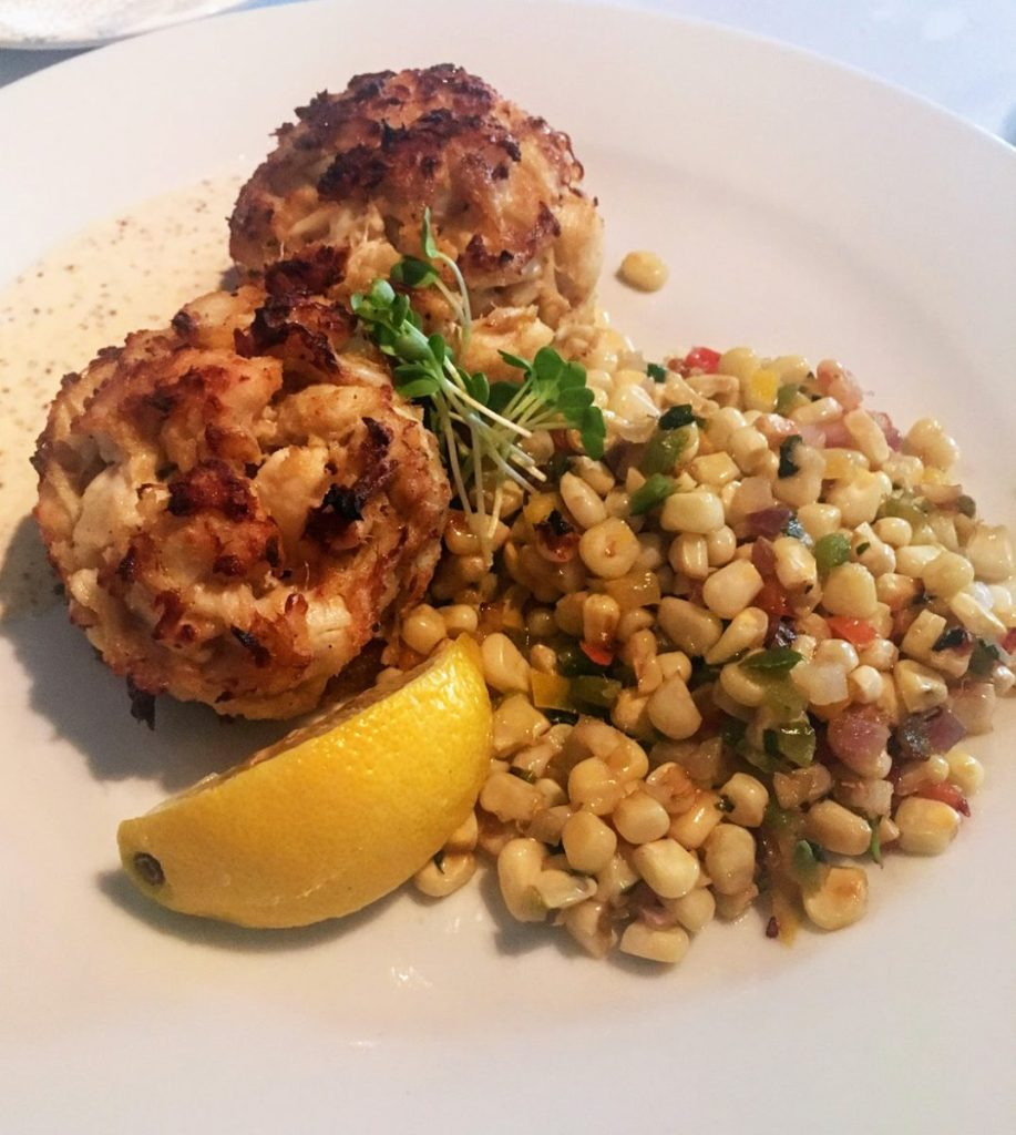 Plate with crab cakes, corn, and a lemon