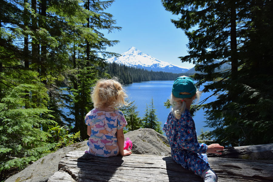 Two children sitting on a rock and enjoying the view of one of Mt. Hood's blue lakes