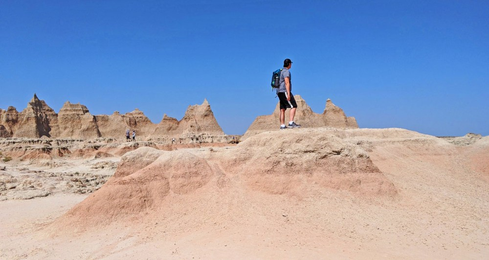 Man standing on a rock formation in Badlands National Park