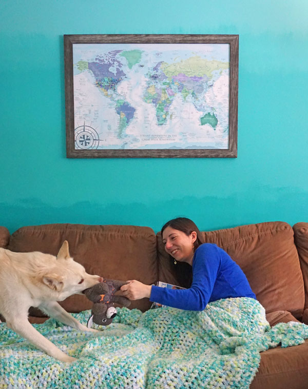 Woman and dog playing with a toy in front of a world travel map