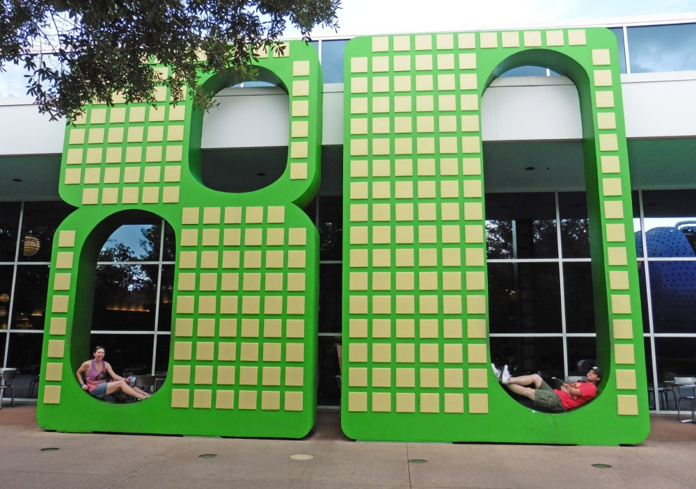 "Couple sitting inside a giant ""80"" at Disney's Pop Century Resort"