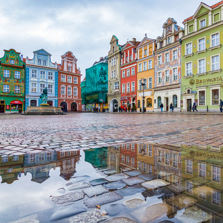 Colorful buildings in old town Poznan, Poland reflected in a puddle
