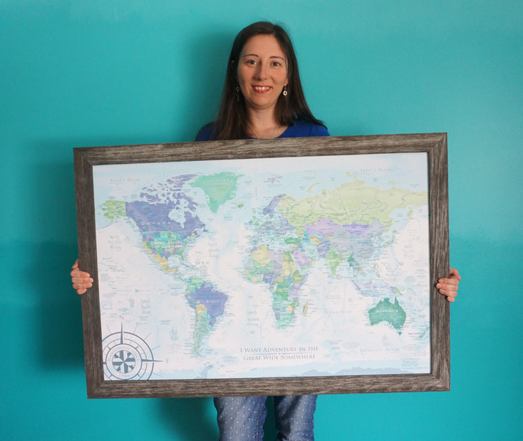Woman holding a framed push pin world map